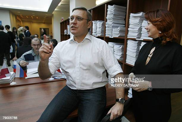 Russian presidential candidate and former Prime Minister Mikhail Kasyanov speaks as his wife Irina stands next to him in front of shelves with lists...