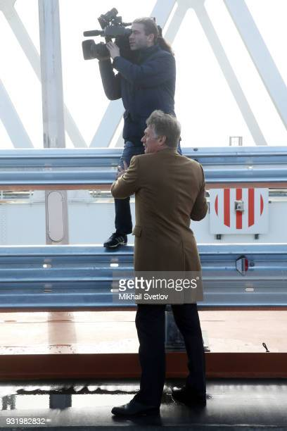 Russian Presidential Press Secretary Dmirty Peskov assists a camearman at the construction site for the Crimean bridge which is being built to...