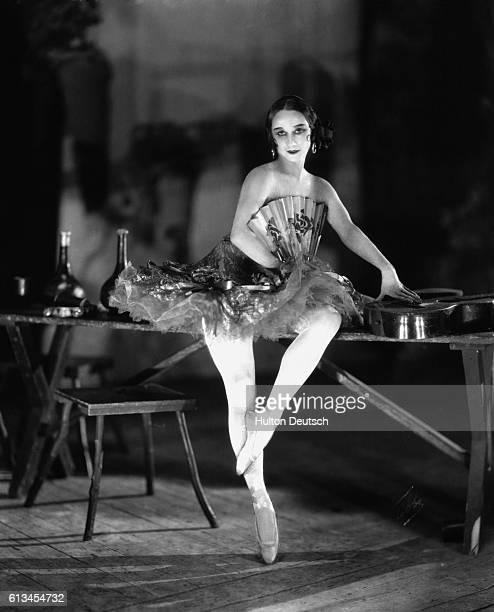 Russian prima ballerina Anna Pavlova poses backstage in costume holding a fan