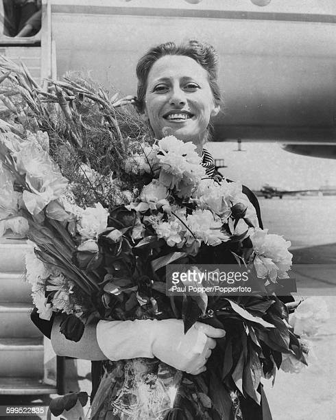 Russian Prima Ballerina Maya Plisetskaya holds a huge bouquet of flowers as she arrives in London with the Bolshoi Ballet Company, London Airport,...