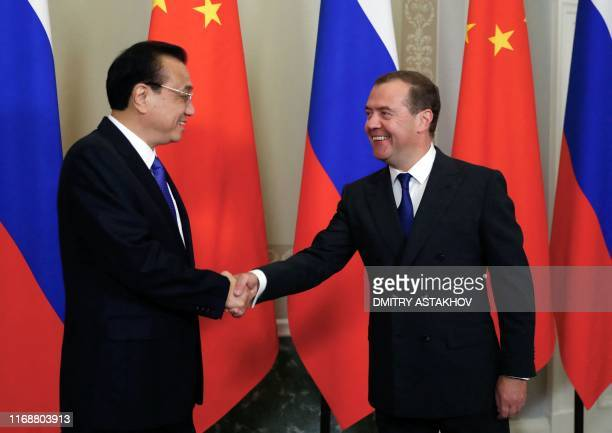 Russian Prime Minister Dmitry Medvedev and Chinese Premier Li Keqiang shake hands during a meeting in Saint Petersburg on September 17 2019