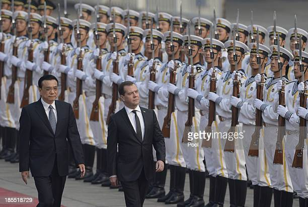 Russian Prime Minister Dmitry Medvedev and Chinese Premier Li Keqiang inspect an honour guard at a welcoming ceremony outside at the Great Hall of...