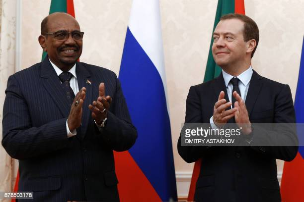 Russian Prime Minister Dmitry Medvedev and Sudanese President Omar alBashir applaud during a signing ceremony following their meeting in Sochi on...