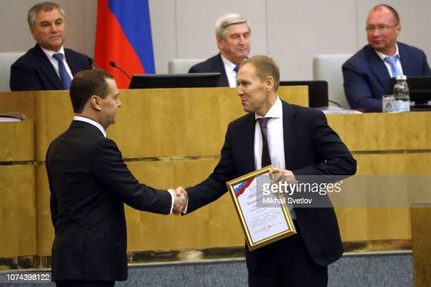Russian Prime Minister Dmitry Medvedev greets just awarded State Duma Deputy Andrey Lugovoy during the plenary meeting of State Duma on December 19...