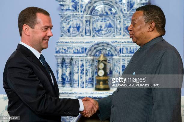 Russian Prime Minister Dmitry Medvedev greets OPEC Secretary General Mohammad Sanusi Barkindo during a meeting at the Gorki residence outside Moscow...