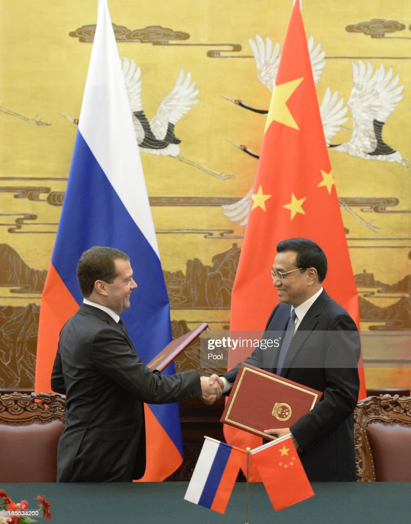 Russian Prime Minister Dmitry Medvedev shakes hands with Chinese Premier Li Keqiang during a signing ceremony at the Great Hall of the People on October 22, 2013 in Beijing, China. Medvedev is in China on a two-day visit as a guest of Chinese Premier Li Keqiang to co-chair the 18th regular meeting between the Chinese and Russian heads of government.
