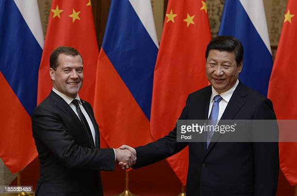 Russian Prime Minister Dmitry Medvedev shakes hands with Chinese President Xi Jinping before a meeting at the Great Hall of the People on October 22,...
