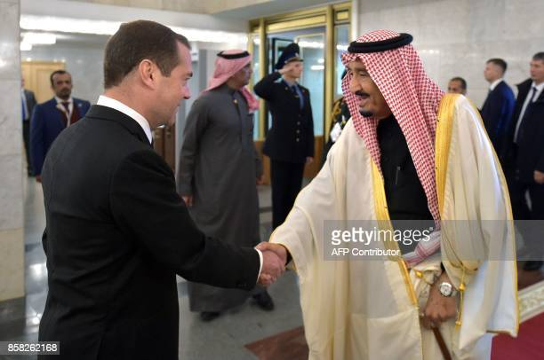 Russian Prime Minister Dmitry Medvedev shakes hands with Saudi Arabia's King Salman bin Abdulaziz Al Saud during a meeting in Moscow on October 6...