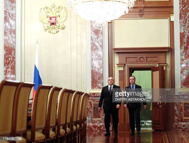 Russian Prime Minister Mikhail Mishustin and deputy head of Russia's Security Council Dmitry Medvedev walk to meet with acting members of the cabinet...