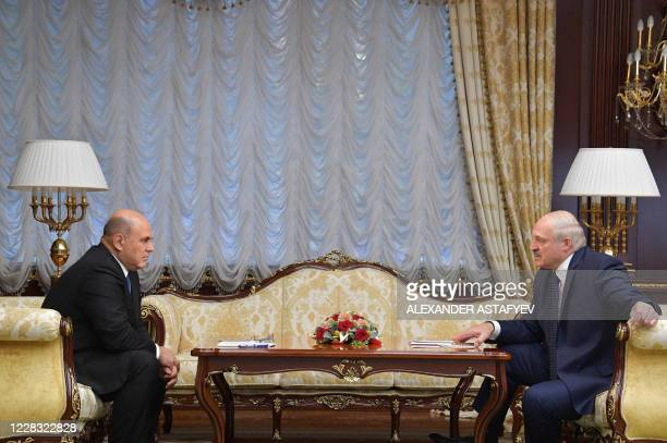 Russian Prime Minister Mikhail Mishustin speaks with Belarus President Alexander Lukashenko during their meeting at the Independence Palace in Minsk...