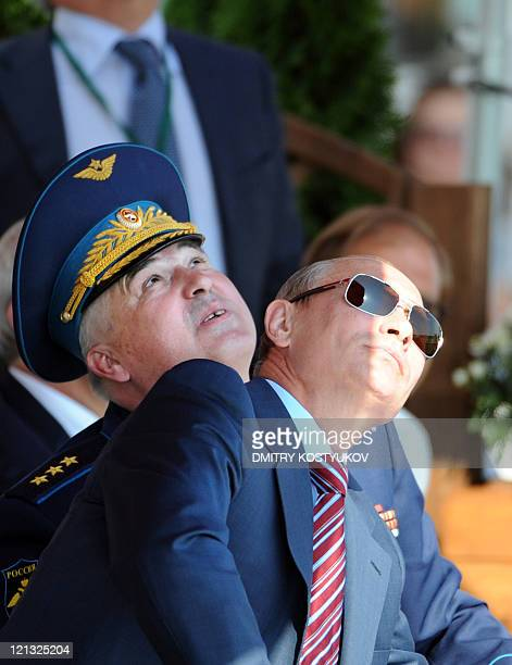 Russian Prime Minister Vladimir Putin and CommanderinChief of the Russian Air Force Alexander Zelin react as they watch an air show during MAKS2011...