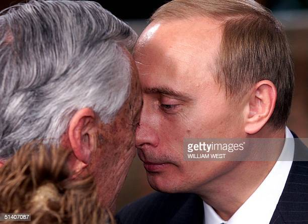 """Russian Prime Minister Vladimir Putin is greeted by a traditional Maori """"hongi"""" - where the pressing of noses symbolically brings the essence of each..."""