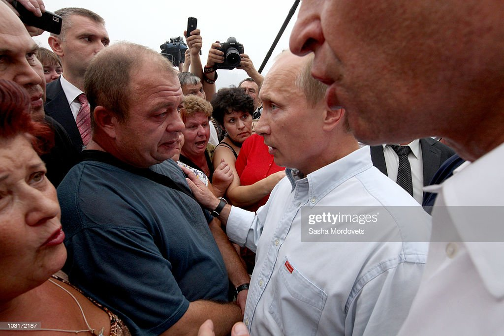 Russian Prime Minister Vladimir Putin (L) meets with people, who suffered from forest fires which swept through their village on July 30, 2010 in Verkhnyaya Vereya, Russia. Putin visited the village where all 341 homes have burned to the ground. The Kremlin called the army to help assist as fires rage over 214,136 acres throughout vast sections of Russia. A state of emergency was ordered on Friday as firefighters continued to save villages and forests from the blaze.