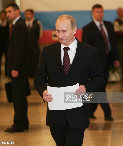 Russian Prime Minister Vladimir Putin prepares to post his ballot at a polling station during municipal elections on October 11 2009 in Moscow Russia...