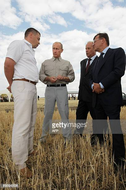 Russian Prime Minister Vladimir Putin speaks with officials during his visit to 'Eksperimentalnoe' farm outside the town of Orenburg on August 4,...