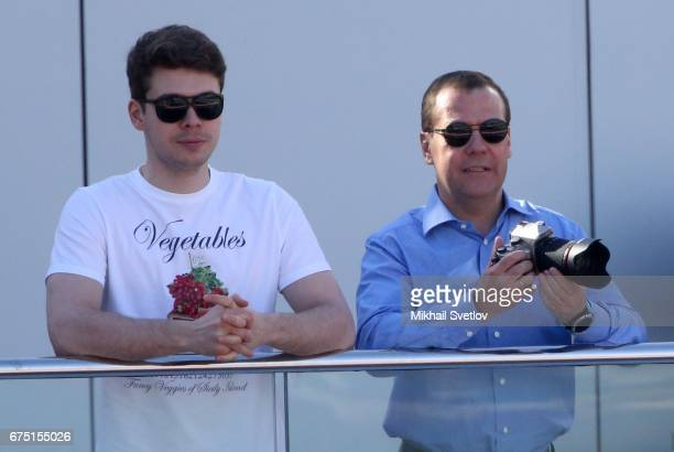 Russian Prime Minsiter Dmitry Medvedev holds a photo camera as he talks to his son Ilya Medvedev during the 2017 Formula 1 Russian Grand Prix race in...