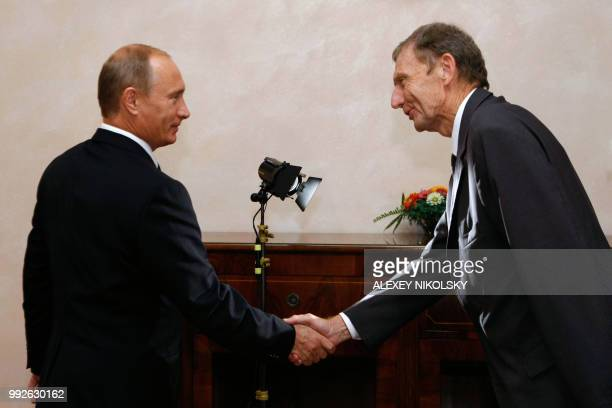 Russian Prime Mninister Vladimir Putin shakes hands with the chief editor Etienne Mougeotte of the French publication Figaro magazine during an...
