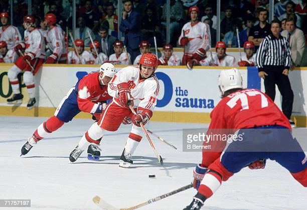 Russian professional hockey player Igor Larionov , center for CSKA Moscow and on the ice as a member of Team USSR, is checked by Canadian hockey...