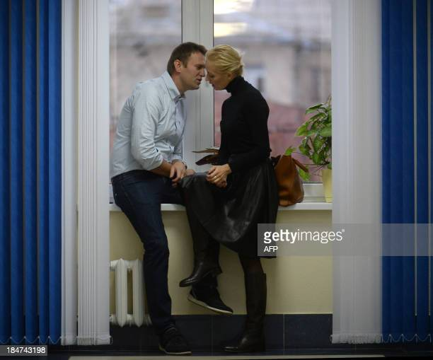 Russian protest leader Alexei Navalny speaks with his wife Yulia during a break at the hearing of his case in a court in the provincial northern city...