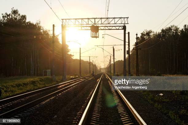 russian railroad track at burning sunset, russian railways surrounded by the forest, moscow oblast, russia - argenberg stock pictures, royalty-free photos & images
