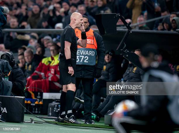 Russian referee Sergei Karasev checks the Video Assistant Referee monitor during the Europa League last 32 first leg football match between FC...