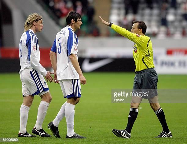 Russian referee Vitaly Doroshenko talks to Ricardo da Silva and Yuris Laizans of FC Shinnik Yaroslavl during the Russian Football League Championship...