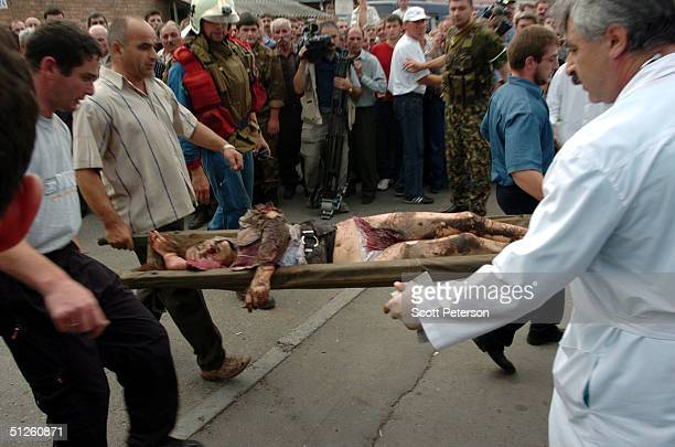 Russian rescue workers remove a body from a school September 3 2004 in Beslan Russia More than 200 people were reportedly killed and at least 700...