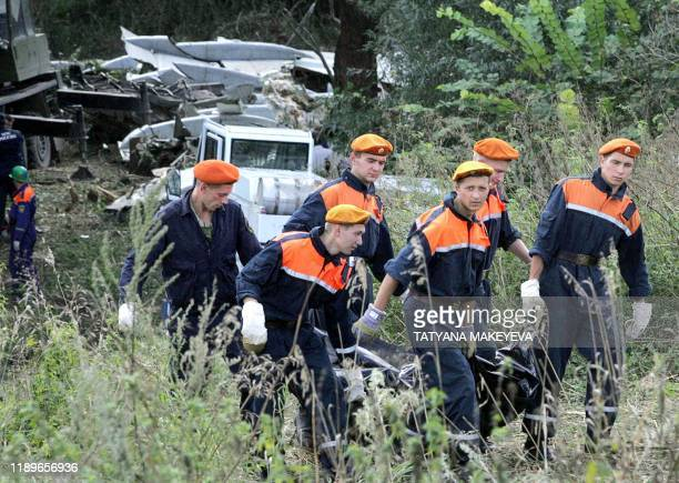 Russian rescuers carry a dead body of the Tupolev 154 passenger jet which crashed near Gluboky a village some 140 km outside Rostov on Don 26 August...