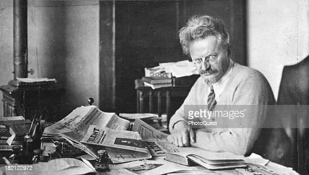 Russian revolutionary and political theorist Leon Trotsky poses at his desk an open newspaper in front of him early to mid 20th century
