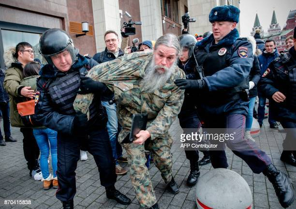 TOPSHOT Russian riot police detain an opposition activist during a protest rally in central Moscow on November 5 2017 / AFP PHOTO / Maxim ZMEYEV