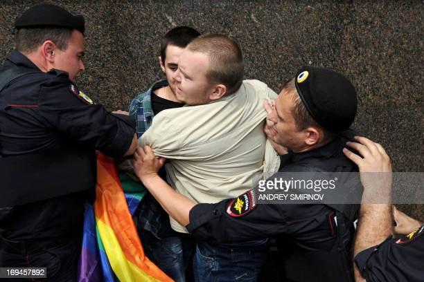 Russian riot policemen detain a gay and LGBT rights activist during an unauthorized gay rights activists rally in cental Moscow on May 25 2013 AFP...