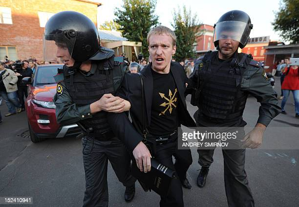 Russian riot policemen detain a member of the Eurasia's youth union political organization during a protest action in front of the Winzavod art...