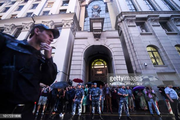 Russian riot policemen stand guard in front of the Russian Supreme court as people holding stuffed toys take part in a rally to demand the release of...