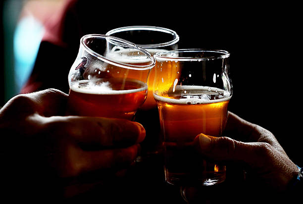 Russian River Brewing Company customers clink their glasses while drinking the newly released Pliny the Younger triple IPA beer on February 7, 2014...