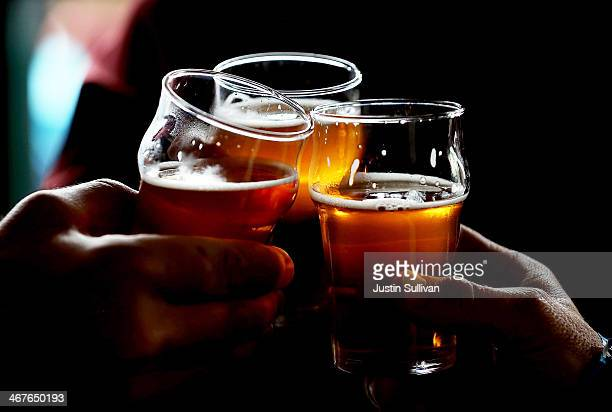Russian River Brewing Company customers clink their glasses while drinking the newly released Pliny the Younger triple IPA beer on February 7 2014 in...