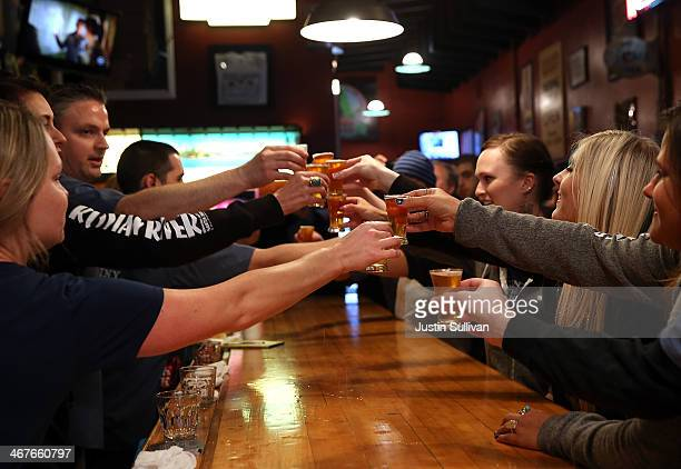Russian River Brewing Company staff members toast the release of Pliny the Younger triple IPA beer before opening the doors to the public on February...