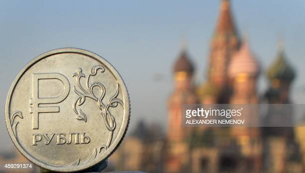 A Russian ruble coin is pictured in front of St Basil cathedral in central Moscow on November 20 2014 After having recently spent billions of dollars...