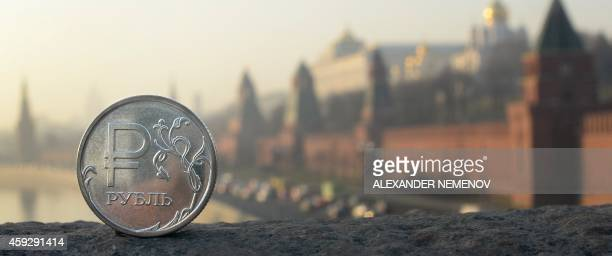 A Russian ruble coin is pictured in front of the Kremlin in central Moscow on November 20 2014 After having recently spent billions of dollars per...