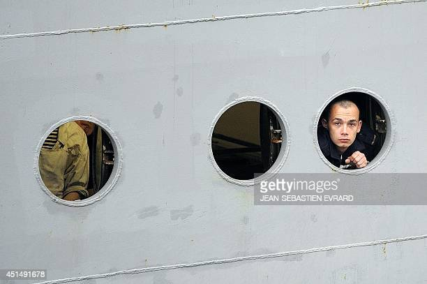 A Russian sailor looks through the porthole as he arrives aboard the Smolniy on June 30 2014 in SaintNazaire western France 400 Russian sailors will...