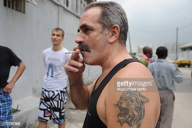 A Russian sailor smokes outside the court premises during the trial of 15 Russian sailors over alleged illegal possession of arms in Lagos on June 18...
