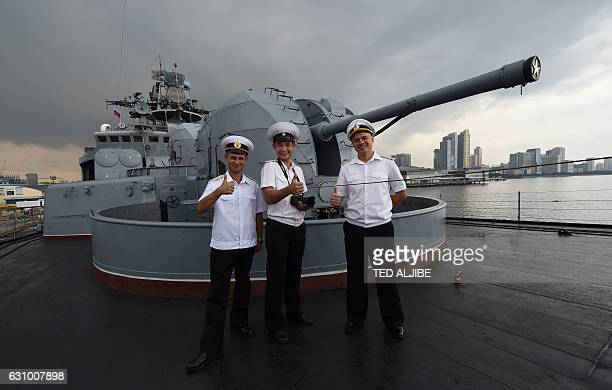 Russian sailors pose for photos at the bow of their antisubmarine ship Admiral Tributs during a public tour at the south pier in Manila on January 5...