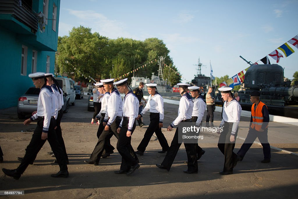 Russian sailors walk across a quayside lined with Russian naval vessels which form part of the Baltic Fleet during Russian Navy day at the Vistula lagoon in Baltiysk, Russia, on Sunday, July 31, 2016. Amid Russia's recent rearmament, the Kaliningrad region has increasingly returned to its Soviet-era role as a garrison on the strategic Baltic Sea coast. Photographer: Andrey Rudakov/Bloomberg via Getty Images