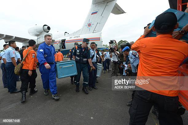A Russian search and rescue team carry their equipment after arriving in a Russian BE200 amphibious aircraft in Pangkalan Bun on January 3 to take...