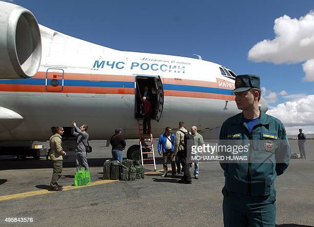 A Russian security guard stands near a plane carrying Russian humanitarian aid in the Yemeni capital Sanaa on November 5 2015 Russia sent a plane to...
