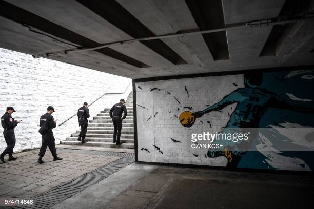 Russian Security officers walk past a graffiti picturing a football player near the Fan zone in Kaliningrad on June 14 2018 during the Russia 2018...