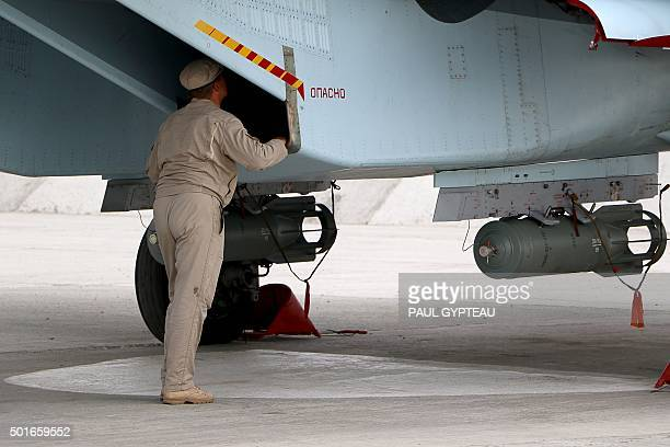 A Russian serviceman prepares a Russian Sukhoi Su30SM fighter jet before departure on a mission at the Russian Hmeimim military base in Latakia...