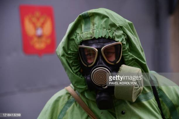 Russian serviceman wearing protective gear disinfects a bus for consripts at a recruiting office in the far eastern city of Vladivostok on June 4...