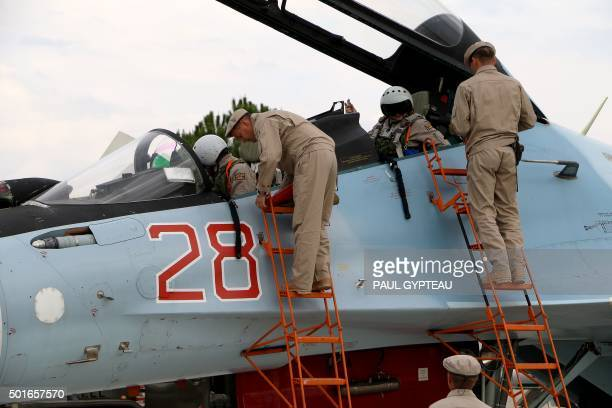 Russian servicemen assist air force pilots in a Russian Sukhoi Su30SM fighter jet before departure on a mission at the Russian Hmeimim military base...