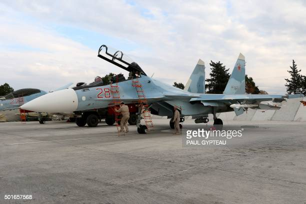 Russian servicemen prepare a Russian Sukhoi Su30SM fighter jet before a departure for a mission at the Russian Hmeimim military base in Latakia...