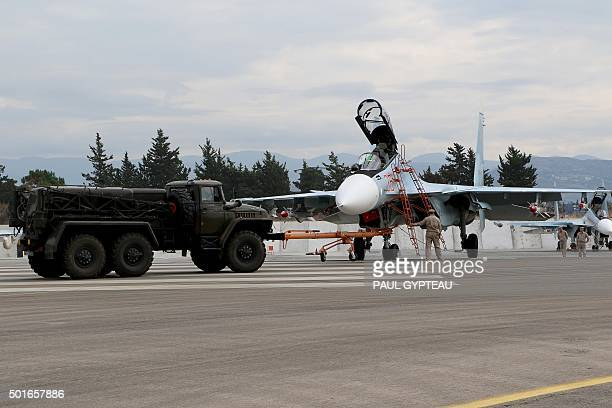 Russian servicemen prepare a Russian Sukhoi Su30SM fighter jet before departure on a mission at the Russian Hmeimim military base in Latakia province...